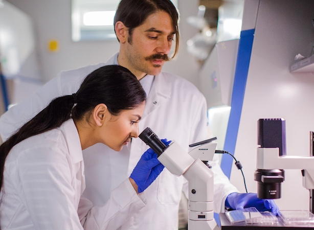 Profile view of female student looking through microscope and man looking at microscope stage next to her.